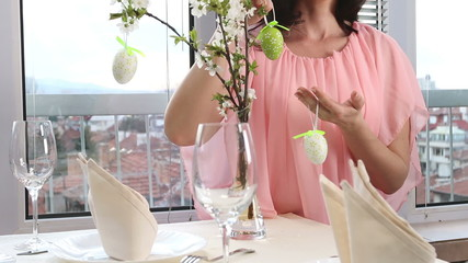 Woman hang easter egg on cherry branch.