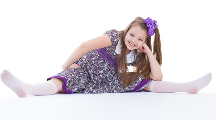 A beautiful young girl sits on a twine.
