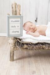 Newborn Baby schlafend in einem Holzbett