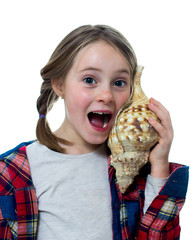 Little girl listening a shell