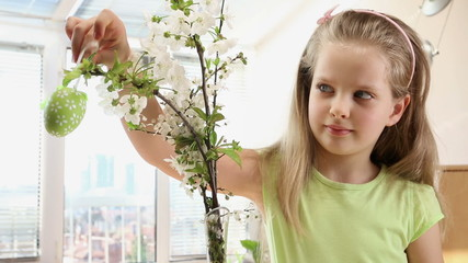 Child hang easter egg on cherry branch.