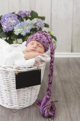 Newborn Baby schlafend in einem Körbchen mit süßer Mütze