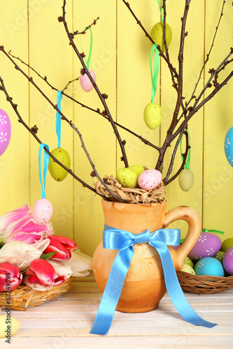 Easter composition with eggs branches on wooden background