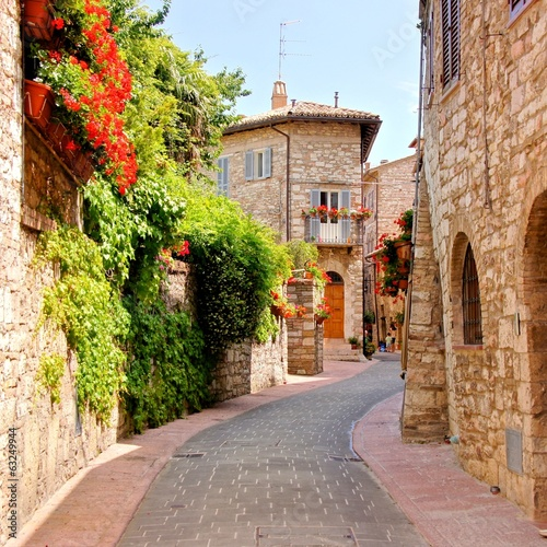 Flower lined street in the town of Assisi, Italy - 63249944