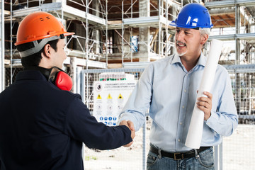 Workers shaking hands in a construction site