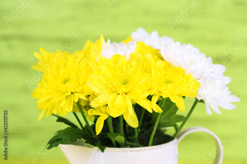Beautiful chrysanthemum flowers in pitcher on wooden background