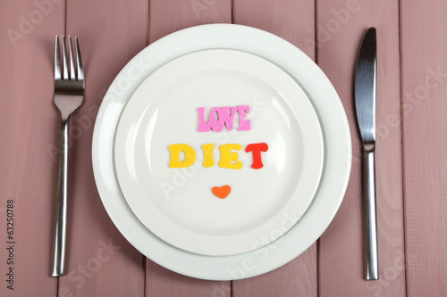Plate with inscription love diet on wooden table close-up