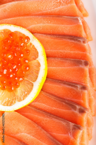 Sliced salmon with lemon and red caviar