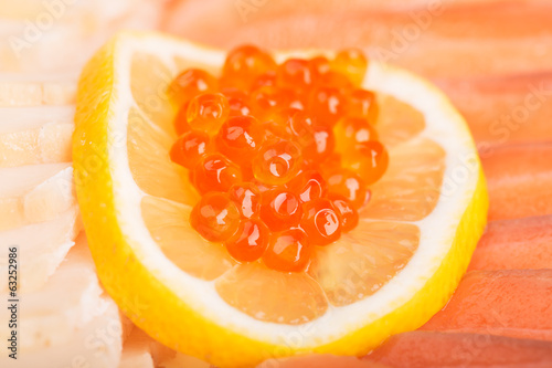 Red caviar on the lemon and sliced fish