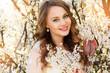 Beautiful girl in blossom cherry garden