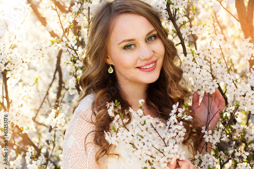 Beautiful girl in blossom cherry garden