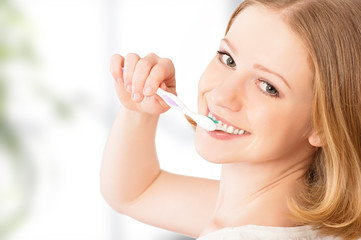 happy woman brushing her teeth with a toothbrush