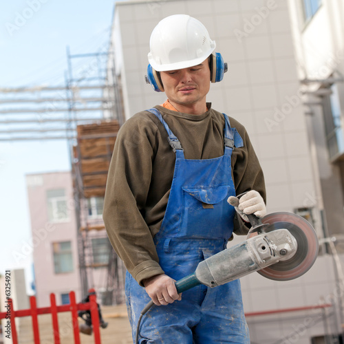 Construction worker with cutting tool angle grinder