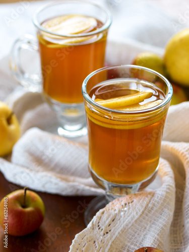 Cup of apple drink and apples on wooden background