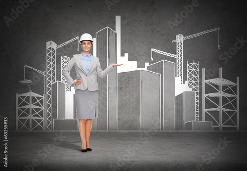 businesswoman in helmet showing construction site