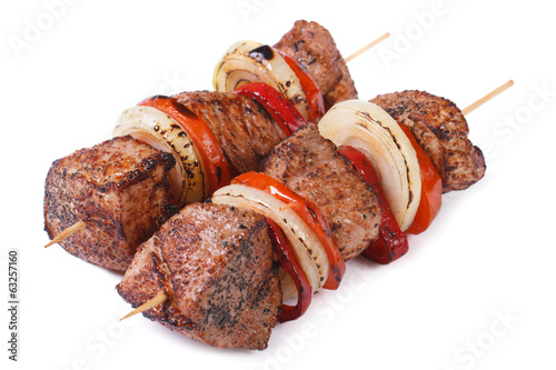 two skewers of meat with vegetables isolated on a white