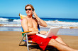 Casual Businessman Relaxing at the Beach with Laptop Computer Ta