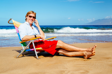 Young Attractive Casual Businessman Relaxing at the Beach Talkin
