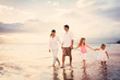 Happy Young Family have Fun Walking on Beach at Sunset - 63257999