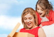 smiling mother and daughter with gift box