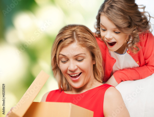 smiling mother and daughter opening gift box