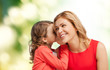 smiling mother and daughter whispering gossip