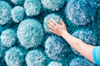 Hand touching fluffy blue carpet with 3D stone like decoration - 63258339