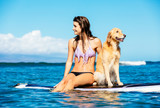 Fototapety Young Woman Surfing with Her Dog
