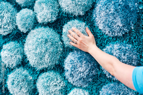 Hand touching fluffy blue carpet with 3D stone like decoration