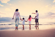 Happy Young Family on Beach at Sunset