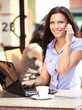 Happy businesswoman talking on the phone in a coffee shop