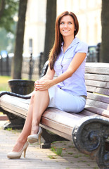 Businesswoman sitting on park bench