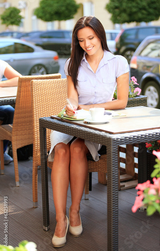 Young professional businesswoman sitting at table at cafe