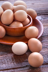 Healthy domestic eggs in a wooden bowl on a rustic table