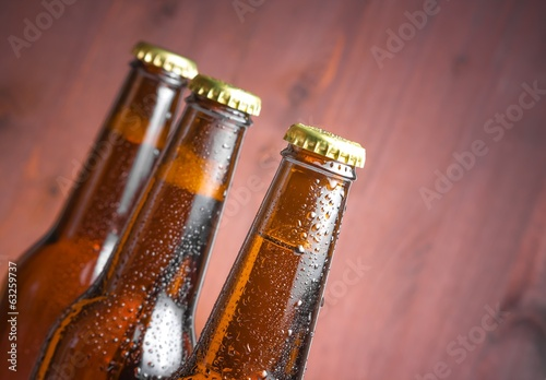 three tilted bottles of fresh beer with drops and space for text