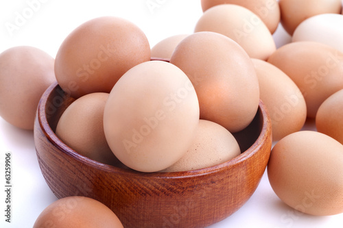 Healthy domestic eggs in a wooden bowl on a white background