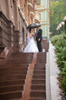 Just married couple kissing on stairway at rainy weather
