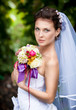 Closeup portrait of cute bride with long veil holding bouquet