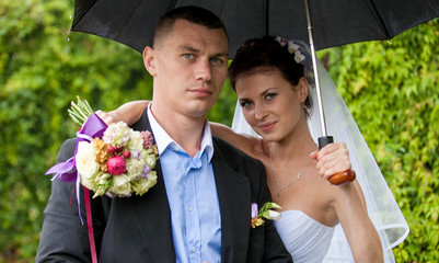 Closeup portrait of just married couple hugging under umbrella