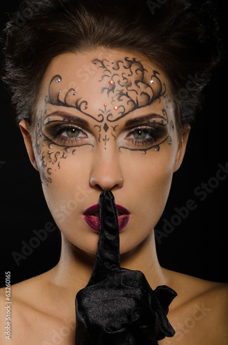 Woman with drawing on face holding finger to lips