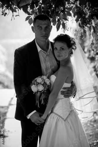 Black and white portrait of bride and groom hugging under tree
