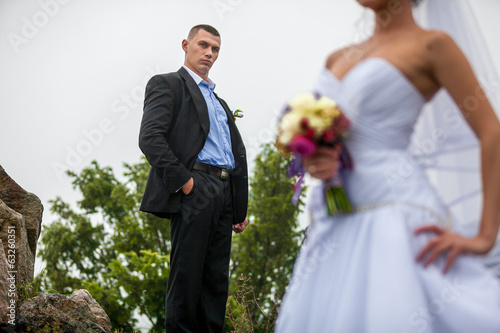 Portrait of groom with bride in blur background