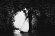 Black and white photo of bride and groom dancing at tree tunnel