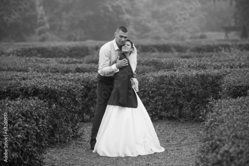 Monochrome photo of groom hugging bride at cold day