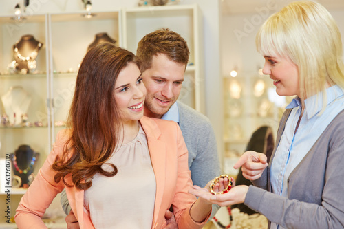 Salesperson showing bracelet to customers