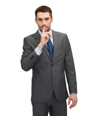 handsome businessman with finger on his lips