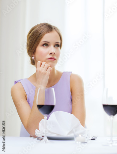 upset woman with glass of whine waiting for date
