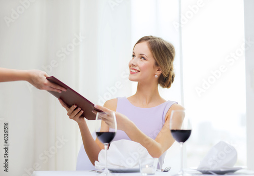 smiling woman giving menu to waiter at restaurant