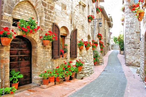 Foto Spatwand Mediterraans Europa Picturesque lane with flowers in an Italian hill town
