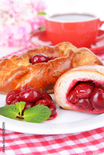 Fresh baked pasties with cherry on plate on table close-up
